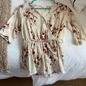 Cream blouse with floral blossoms and roots.